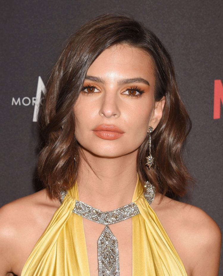 Emily Ratajkowski attends The Weinstein Company and Netflix Golden Globe Party wearing a golden dress with a wavy bob hairstyle.