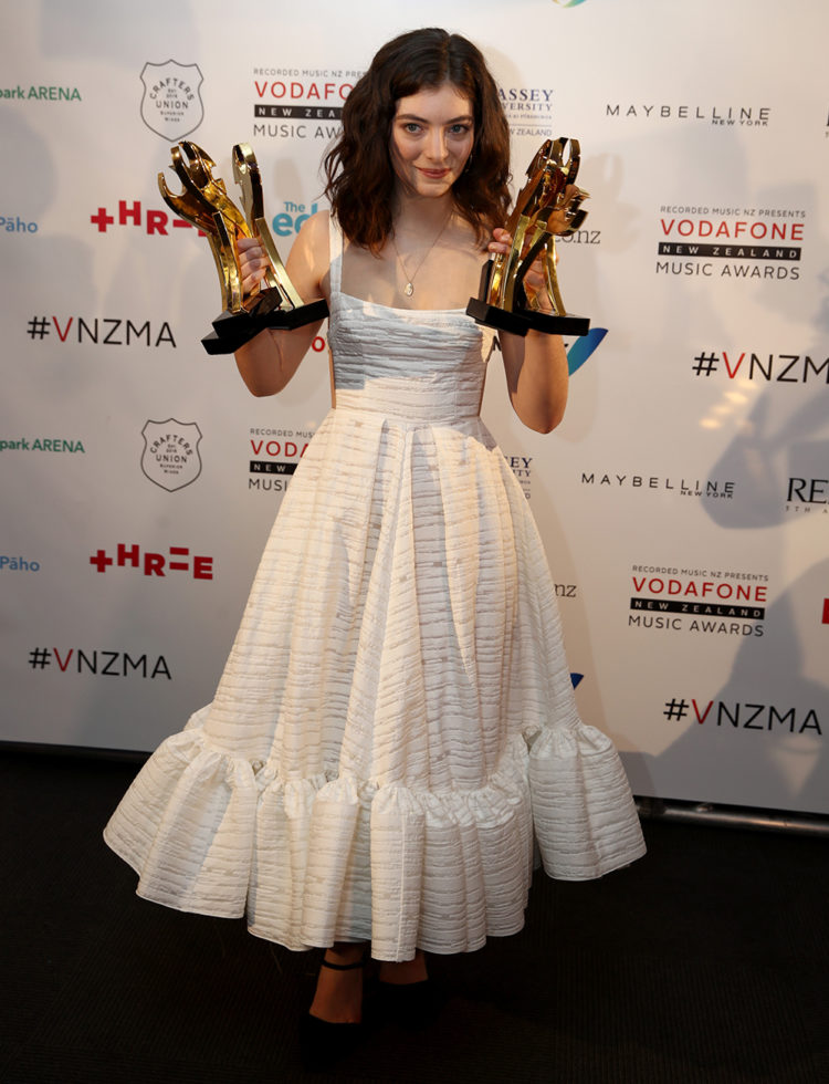 Lorde wears a white dress with stripe detailing and a peplum hem at the VNZMAs.