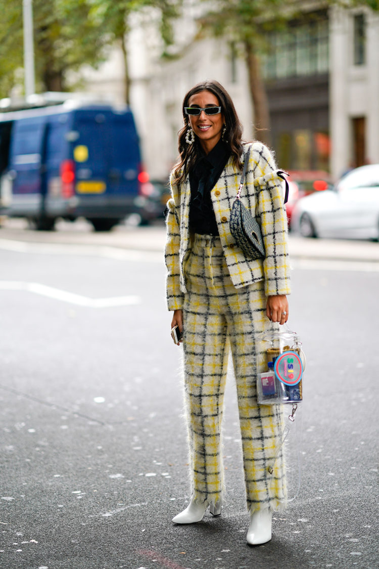 A guest wears a Dior bag, a yellow checked jacket pants, white shoes, during London Fashion Week September 2018 on September 14, 2018 in London, England. (Photo by Edward Berthelot/Getty Images)