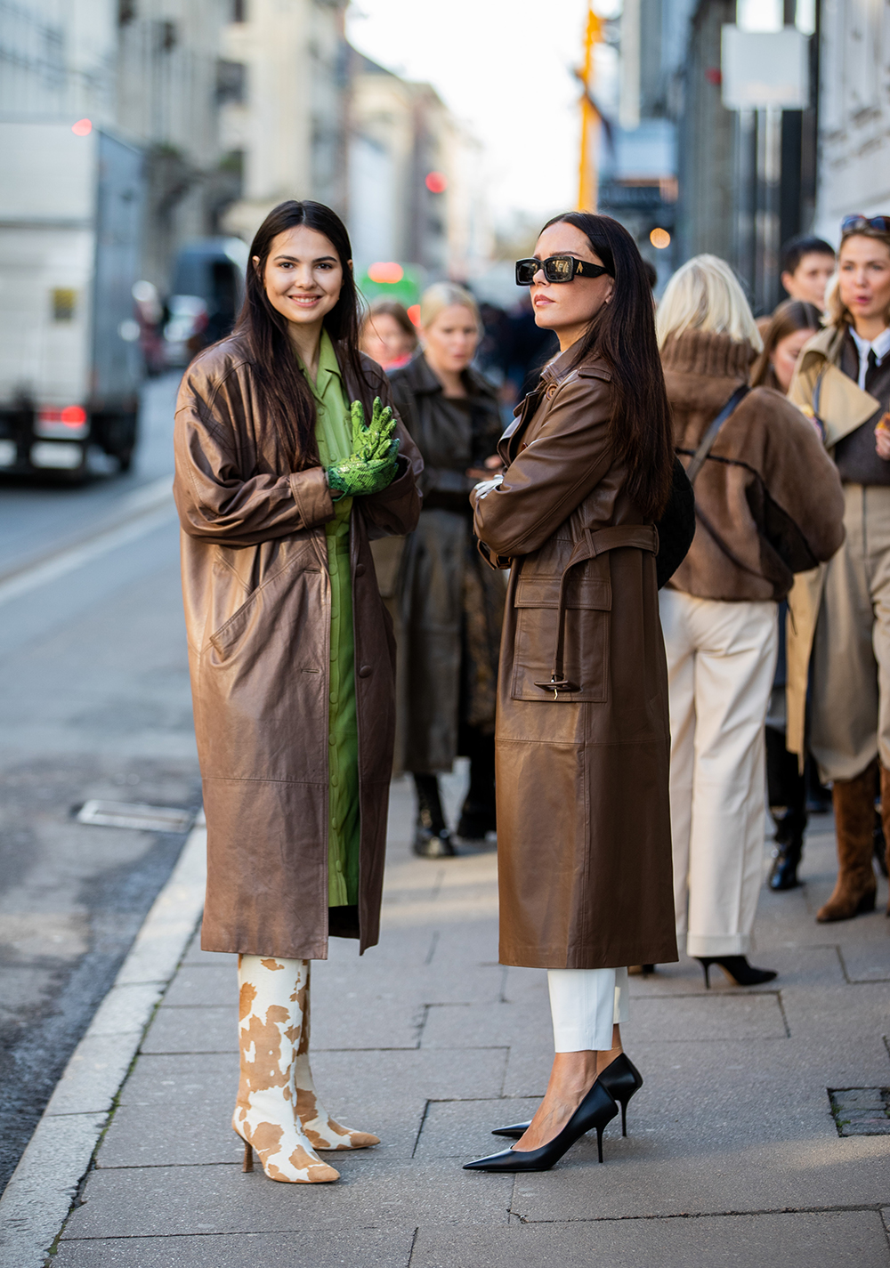 COPENHAGEN, DENMARK - JANUARY 29: Doina Ciobanu seen wearing brown coat, green dress, gloves with snake print, boots with cow print and Evangelie Smyrniotaki wearing brown coat, white pants, heels outside REMAIN Birger Christensen during Copenhagen Fashion Week Autumn/Winter 2020 Day 2 on January 29, 2020 in Copenhagen, Denmark. (Photo by Christian Vierig/Getty Images)